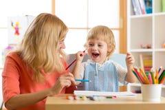 A mãe da família e o filho felizes da criança pintam junto A mulher ajuda o menino da criança fotografia de stock