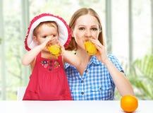 Mãe da família e suco de laranja bebendo da filha do bebê na soma Fotografia de Stock Royalty Free