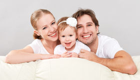 Mãe da família, pai, filha do bebê da criança em casa no sofá que joga e riso felizes Imagens de Stock