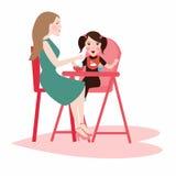 A mãe da mamã dá o alimento a sua filha da menina, tem um alimento de café da manhã que senta-se na cadeira alta das crianças imagens de stock royalty free