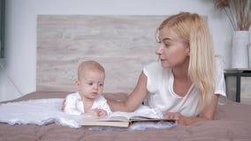 A mãe de amor com livro diz a história do conto de fadas à filha do bebê que encontra-se na cama em casa