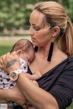 Mãe de amor que embala seu bebê em seu ombro fora fotos de stock