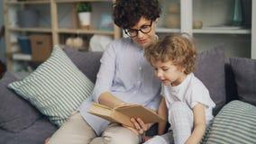 Mãe de amor que ensina seu filho ler guardar o livro que fala no sofá em casa