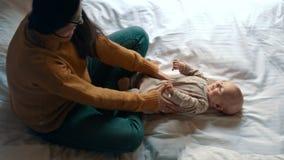 Mãe de amor que joga com o bebê na cama Mãe de sorriso da criança recém-nascida filme
