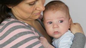 Mãe de cabelos compridos preto-de cabelo bonita nova com o bebê recém-nascido de dois meses engraçado em seus braços A mamã balan video estoque