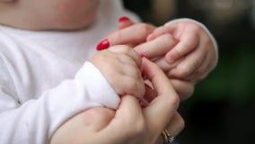 Mãe de inquietação com bebê, conceito do amor e família mãos do close up da mãe e do bebê, em conjunto Cuidado da matriz filme