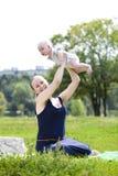 A mãe de inquietação está mantendo o bebê, contra o parque do verão Foto de Stock Royalty Free