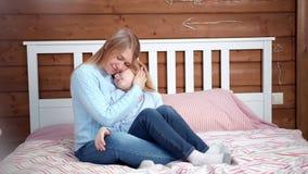 Mãe de inquietação nova que abraça e que beija sua filha pequena que tem o tiro completo do melhor sentimento filme