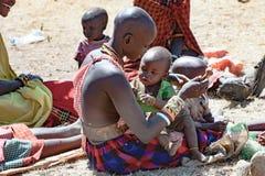 Mãe de Maasai que joga com bebê, Tanzânia imagem de stock