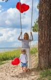Mãe de Oung e criança pequena com os balões vermelhos do coração na praia Imagem de Stock Royalty Free