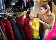 A mãe de sorriso com filha está comprando a camiseta morna Fotos de Stock Royalty Free