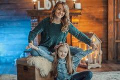 Mãe de sorriso com sua filha na sala no tapete Fotografia de Stock