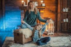Mãe de sorriso com sua filha na sala no tapete Fotos de Stock