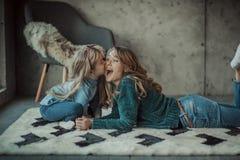 Mãe de sorriso com sua filha na sala no tapete Fotos de Stock Royalty Free