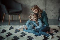 Mãe de sorriso com sua filha na sala no tapete Foto de Stock