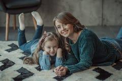 Mãe de sorriso com sua filha na sala no tapete Imagem de Stock Royalty Free