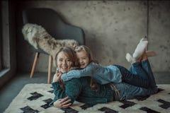 Mãe de sorriso com sua filha na sala no tapete Imagens de Stock Royalty Free