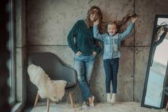 Mãe de sorriso com sua filha na sala no tapete Imagem de Stock