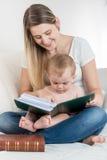 Mãe de sorriso e seus 9 meses do bebê idoso que senta-se no sofá e Fotografia de Stock Royalty Free