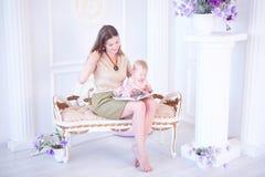 A mãe de sorriso e sua filha pequena leram um livro sobre Imagem de Stock Royalty Free