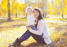 Mãe de sorriso feliz com a criança pequena que joga no outono ensolarado foto de stock
