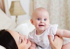 Mãe de sorriso feliz com o bebê idoso de seis meses Imagens de Stock Royalty Free
