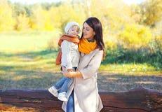 A mãe de sorriso feliz que guarda sobre entrega a criança no outono imagem de stock