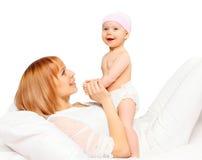 Mãe de sorriso feliz que joga com o bebê na cama Fotos de Stock