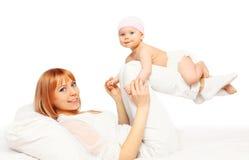 Mãe de sorriso feliz que joga com o bebê na cama Imagens de Stock
