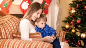 Mãe de sorriso feliz que senta-se na poltrona com seus filho pequeno e vídeo de observação no smartphone Árvore de Natal e video estoque