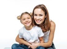 Mãe de sorriso que abraça a filha imagens de stock royalty free