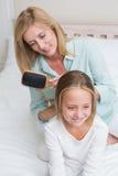 Mãe de sorriso que escova seu cabelo das filhas foto de stock royalty free