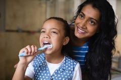 Mãe de sorriso que está pelos dentes de escovadela da filha no banheiro imagens de stock royalty free