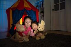 Mãe de sorriso que guarda o brinquedo da peluche com filha Imagem de Stock Royalty Free