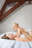 Mãe de sorriso que guardara o bebê bonito na cama foto de stock royalty free