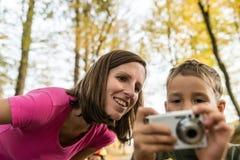 A mãe de sorriso que olha uma imagem em uma câmera guardou por seus jovens Foto de Stock