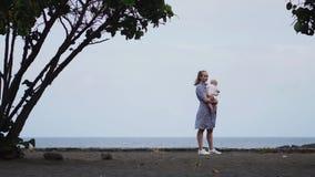 Mãe devotada e bebê que afagam, passando o tempo da qualidade da ligação observando o cloudscape azul brilhante Parenting atento video estoque