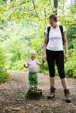 Mãe devotada que guarda as mãos com seu filho, andando nas madeiras imagem de stock royalty free
