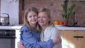 Mãe do amor, retrato da mamã feliz com a filha pequena que abraça e beijos no mordente na cozinha em casa