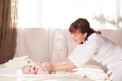A mãe do bebê do rapaz pequeno que faz as mãos e os pés da massagem Foto de Stock Royalty Free