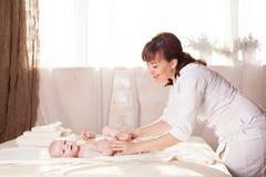 A mãe do bebê do rapaz pequeno que faz as mãos e os pés da massagem Imagem de Stock