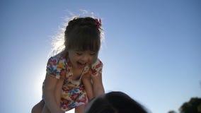 Mãe do close-up que levanta a filha pequena no ar vídeos de arquivo