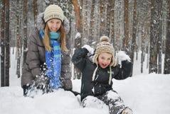 A mãe do inverno com seu filho concede o assento na neve no wo Imagens de Stock Royalty Free
