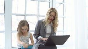 Mãe do negócio com o portátil e a filha que sentam-se pela janela vídeos de arquivo