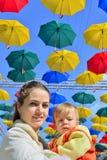 Mãe do retrato com a criança na rua decorada com guarda-chuvas coloridos Fotografia de Stock