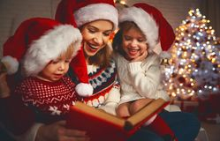 A mãe e as crianças da família leram um livro no Natal perto do firep Fotos de Stock