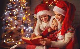 A mãe e as crianças da família leram um livro no Natal perto do firep Foto de Stock