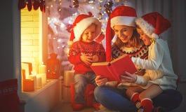 A mãe e as crianças da família leram um livro no Natal perto do firep Fotografia de Stock