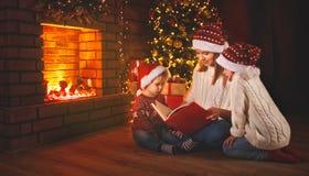 A mãe e as crianças da família leram um livro no Natal perto do firep Imagens de Stock