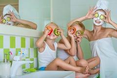 A mãe e as crianças fazem uma máscara protetora na manhã As crianças que gracejam com sua mamã Tratamentos da beleza para a pele fotografia de stock
